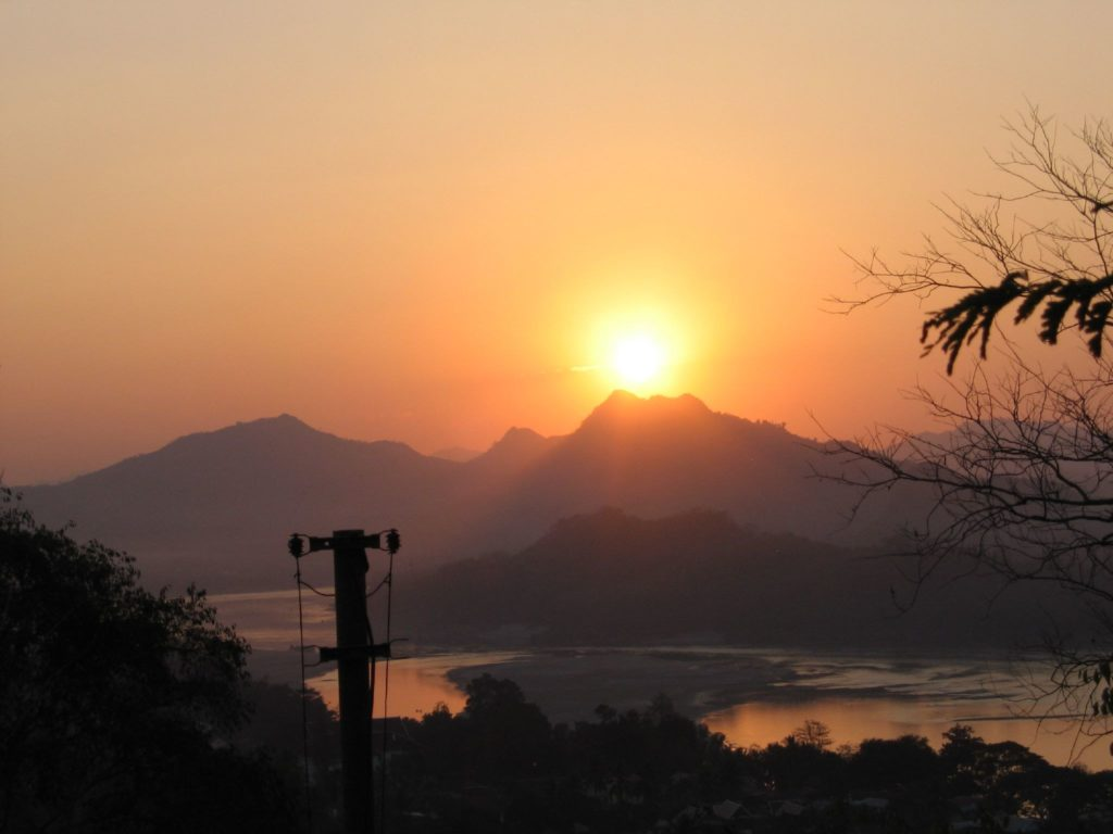 Sun setting over LuangPrabang, as seen from Phu Si Hill. Image courtesy of Shannon Shue/Creative Commons