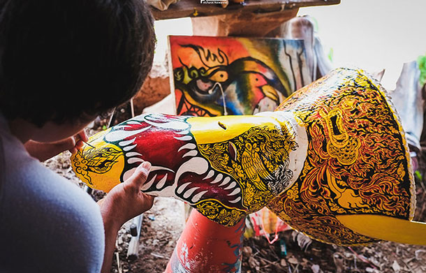 Artisan prepares intricately decorated Phi Ta Kon mask. Image courtesy of the Tourism Authority of Thailand.